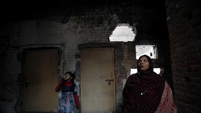 In this Saturday, Jan. 11, 2014, photo, Pakistani Christian, Nomi Shahid and her daughter Aliza, stand at their house, which was torched by radical Muslim's mob last March, in Lahore. Pakistan's blasphemy law has become a potent weapon in the arsenal of Muslim extremists, who use it against adherents of minority religions. (AP Photo/Anjum Naveed)