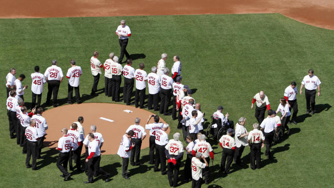 Former Boston Red Sox players, mangers and coaches gather on the field during ceremonies to celebrate the 100th anniversary of the first regular season baseball game at Fenway Park, before a game between the New York Yankees and the Red Sox in Boston, Friday, April 20, 2012. (AP Photo/Michael Dwyer)
