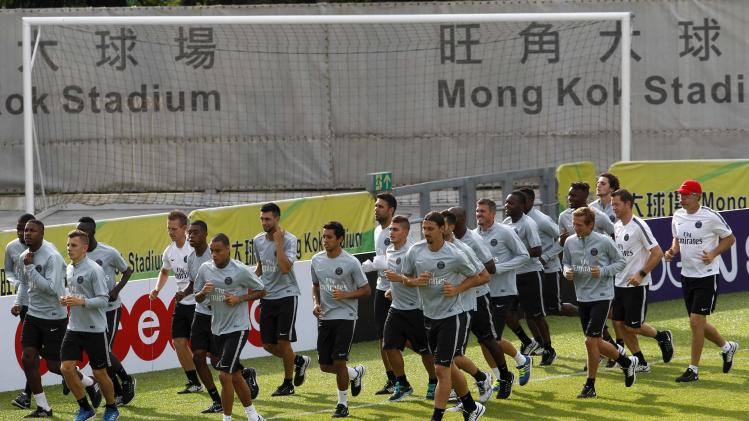 Paris Saint-Germain soccer players warm up during a training session in Hong Kong