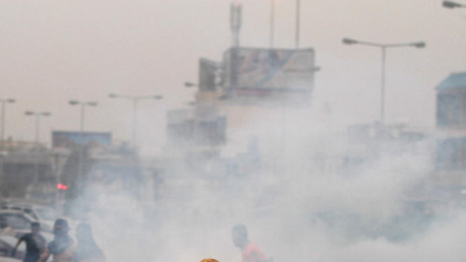 Anti-government protesters run through tear gas fired by riot police Friday, April 20, 2012, to prevent them from marching toward the hub of last spring's pro-democracy uprising at the end of a mass rally just outside Manama, Bahrain. Tens of thousands of anti-government protesters flooded a major highway in Bahrain demanding a halt to the Formula One race on its first day of practice runs, as the Gulf kingdom's crown prince vowed the country's premier prestige sporting event would go ahead. (AP Photo/Hasan Jamali)
