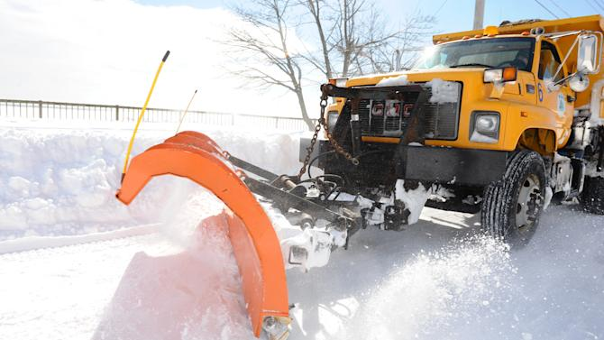 A city plow speeds by on Beach Street after a blizzard pounded the region, Saturday, Feb. 9, 2013 in West Haven, Conn. The storm dumped at least 2 feet of snow throughout Connecticut, paralyzing much of the state. The governor ordered all roads closed Saturday until further notice, and even emergency responders were stuck on highways. (AP Photo/The Connecticut Post, Christian Abraham) MANDATORY CREDIT: CHRISTIAN ABRAHAM/CONNECTICUT POST