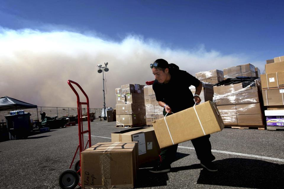 Smoke rises in the background as Indiara Modesto works outside the supply unit area at Centennial High School, the Carpenter 1 fire command center, in Las Vegas on Monday, July 8, 2013. The wildfire, which encompasses thousands of acres, began last Monday. (AP Photo/Las Vegas Review-Journal, Jessica Ebelhar)