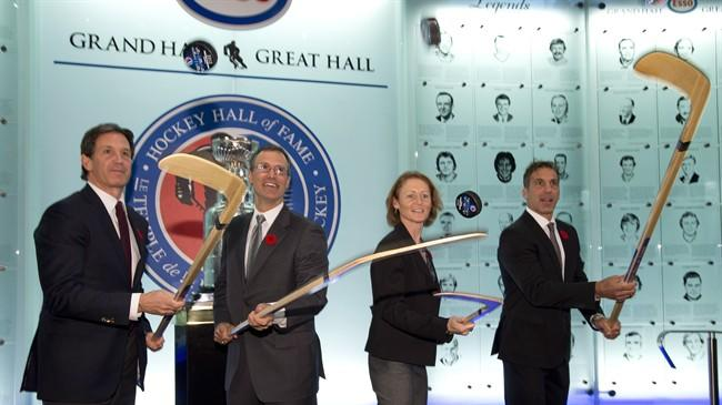 Hockey Hall of Fame inductees (left to right) Brendan Shanahan,Scott Niedermayer, Geraldine Heaney and Chris Chelios flip pucks after being presented with their rings at the Hall in Toronto on Friday November 8, 2013. THE CANADIAN PRESS/Frank Gunn