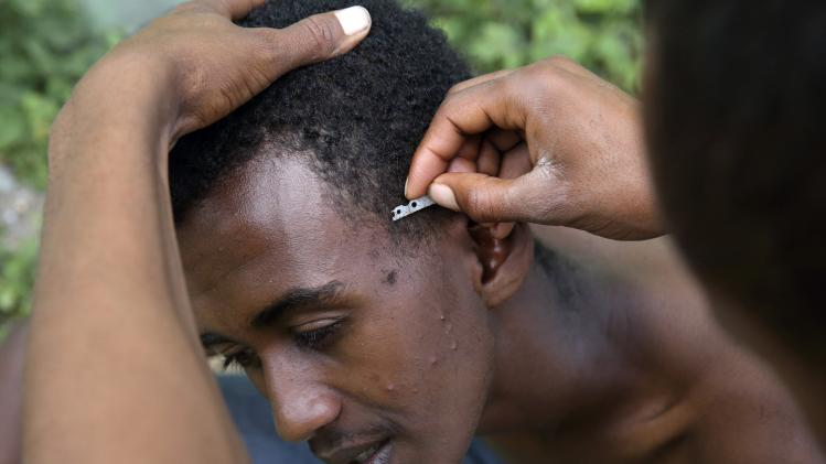 "An Eritrean migrant shaves his friend's hair in the ""jungle"" close to a chemical factory in Calais"