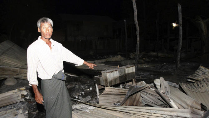 A Muslim man shows his burnt residence in Htan Gone village of Kantbalu township, Sagaing division Myanmar, Sunday, Aug. 25, 2013. Hundreds of Buddhists carrying sticks and swords went on a rampage in a village in northwestern Myanmar, torching dozens of homes and shops following rumors that a young woman had been sexually assaulted by a Muslim man, police and witnesses said Sunday. (AP Photo/Khin Maung Win)