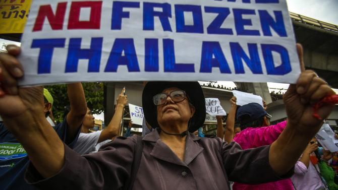 A demonstrator holds up a sign as she joins others during a protest against military rule at Victory Monument in Bangkok