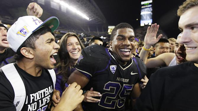 Fans surround Washington's Bishop Sankey after fans ran onto the field to celebrate Washington's 17-13 upset of Stanford in an NCAA college football game, Thursday, Sept. 27, 2012, in Seattle. (AP Photo/Ted S. Warren)