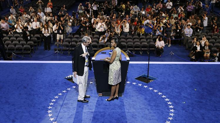 First Lady Michelle Obama listens to a production manager during a sound check for the Democratic National Convention in Charlotte, N.C., on Monday, Sept. 3, 2012. (AP Photo/Charlie Neibergall)