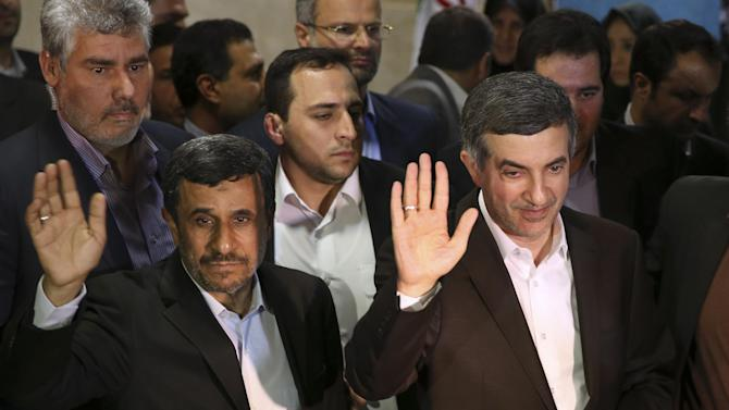 In this picture taken on Saturday, May 11, 2013, Iranian President Mahmoud Ahmadinejad, left, and his close ally Esfandiar Rahim Mashaei wave to journalists as they arrive at the election headquarters of the interior ministry for registering Masheaei's candidacy for the upcoming presidential election, in Tehran, Iran.  By now, President Mahmoud Ahmadinejad is well accustomed to enduring blows from Iran's ruling clerics as his reputation fell from favored son to political outcast. But their intended parting shot _ barring his chief aide from the presidential race _ may be just the opening act in Ahmadinejad's reinvention as a self-styled opposition force. (AP Photo/Ebrahim Noroozi)