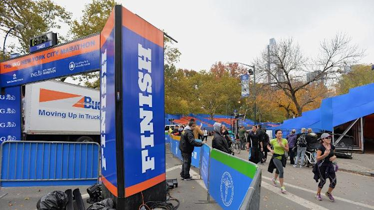 People jog near the finish line of the New York City Marathon in New York on October 31, 2013, as preparations continue for the November 3 race