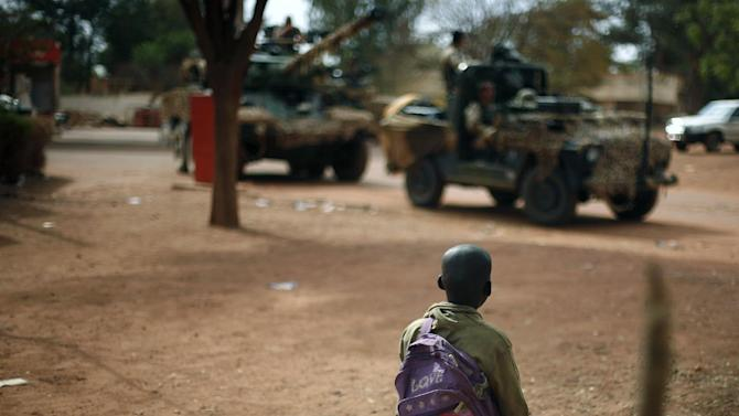 A child looks at French soldiers filling up their tank at a local petrol station in Sevare, some 620 kilometers (385 miles) north of Mali's capital Bamako, Friday, Jan. 25, 2013. The French currently have some 2,400 forces in the country and have said that they will stay as long as needed in Mali, a former French colony. However, they have called for African nations to take the lead in fortifying the Malian army's efforts. (AP Photo/Jerome Delay)