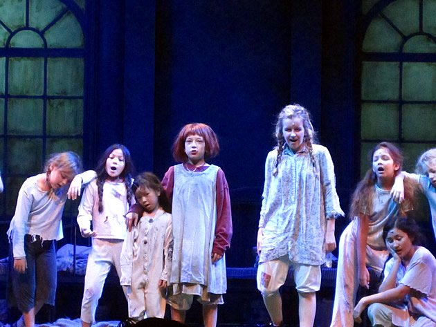"Chloe (standing beside Ella Crossland, who plays ""Annie"") pulls a glum expression as the orphans sing ""It's a Hard Knock Life"". (Yahoo! photo)"