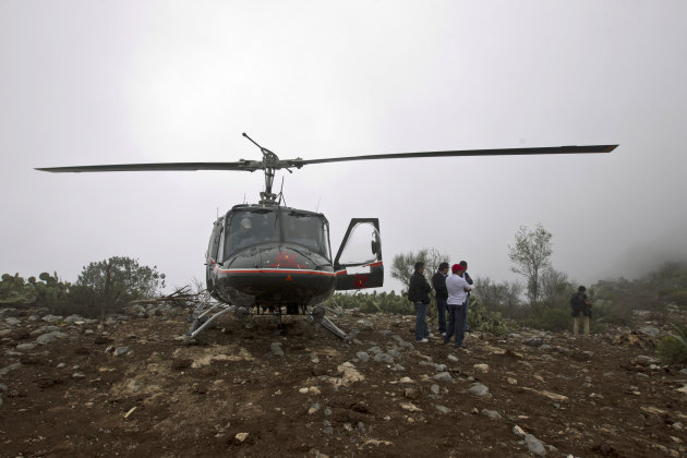 A rescue helicopter with members of the Mexican General Civil Aeronautic Directorate (DGAC) stand on top of the hill right next to the canyon where U.S.-born singer Jenni Rivera's jet crashed near the
