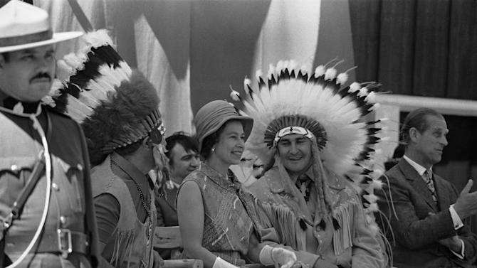 """FILE In this July 3, 1973 photo, Chief Frank Pelletier is shown with Britain's Queen Elizabeth II in Thunder Bay, Ontario, as she views the display of Appaloosa horses and aboriginal Canadian traditional dancing.  Decades have passed since Canadians replaced """"God Save the Queen"""" with """"O Canada,"""" but royalty-lovers are in for a thrill Thursday, June 30, 2011,  when Prince William and his bride come visiting.  Those who leaf through the country's updated citizenship guide will find the oath of allegiance to Queen Elizabeth II is now at the front.  The pamphlet is a reflection of something deeper ,   Prime Minister Stephen Harper's ambition to foster a conservative national identity in which the royal connection plays a key role. (AP Photo)"""