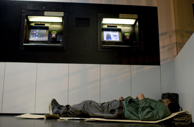 A homeless man sleeps on a piece of cardboard next to cash dispenser, in Pamplona, northern Spain, Tuesday, Oct. 23, 2012. Spain's economy continued to shrink in the third quarter, contracting by 0.4 percent compared with the previous three months, according to central bank estimates Tuesday that will increase pressure on Prime Minister Mariano Rajoy to seek financial help from Europe(AP Photo/Alvaro Barrientos)
