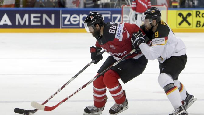 Canada's Burns fights for the puck with Germany's Rieder during their Ice Hockey World Championship game at the O2 arena in Prague