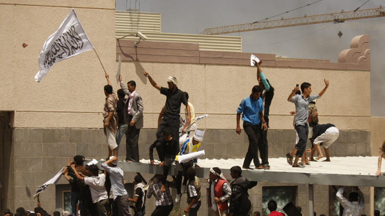 "A Yemeni protestor, left, holds a white flag with Islamic inscription in Arabic that reads, ""No God but Allah, and Mohammed is his prophet,"" in front of the U.S. embassy during a protest about a film ridiculing Islam's Prophet Muhammad, in Sanaa, Yemen, Thursday, Sept. 13, 2012. Dozens of protesters gather in front of the US Embassy in Sanaa to protest against the American film ""The Innocence of Muslims"" deemed blasphemous and Islamophobic. (AP Photo/Hani Mohammed)"
