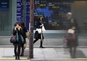 Pedestrians stand in front of a stock quotation board displaying stock prices outside a brokerage in Tokyo