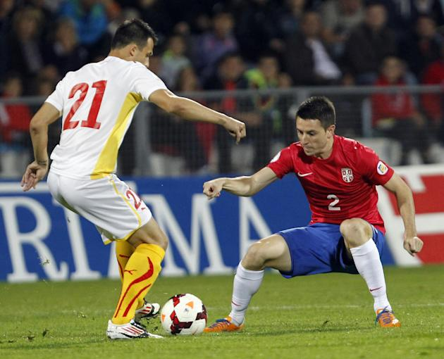 Serbia's Antonio Rukavina, right, challenges for the ball with Macedonia's Mirko Ivanovski during their World Cup 2014 Group A qualifying soccer match at the City Stadium in Jagodina, Serbia, Tuesday,