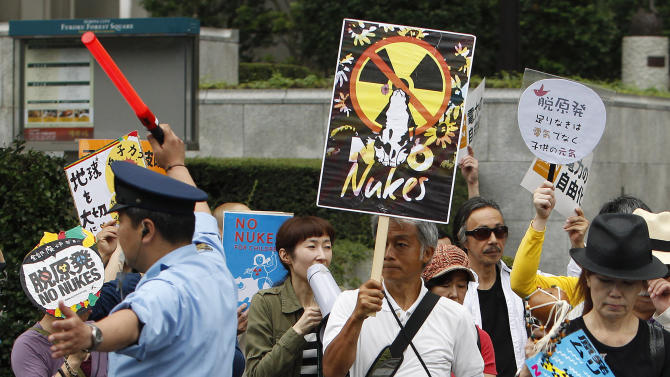 Demonstrators walk past the headquarters of Tokyo Electric Power Co. (TEPCO) during their anti-nuclear power protest in Tokyo Sunday, June 26, 2011. (AP Photo/Shizuo Kambayashi)