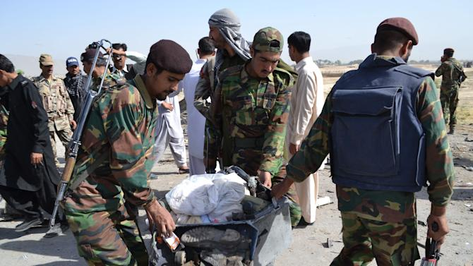 Pakistani security personnel carry a victim's belongings at the site of bombing in Quetta, Pakistan on Thursday, May 23, 2013. A car bomb targeting a police vehicle killed 11 policemen and one civilian Thursday in an area of southwest Pakistan wracked by a separatist insurgency and Islamic militancy, police said. (AP Photo/Arshad Butt)