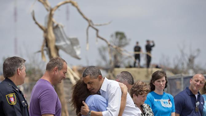 President Barack Obama embraces a school official as he views the devastation of the Plaza Towers Elementary School, Sunday, May 26, 2013, in Moore, Okla., caused by tornado and severe weather last week.  (AP Photo/Carolyn Kaster)