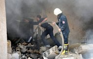 Damascus firemen extinguish flames on September 25 at a military administration building that partially collapsed following an explosion in this photo released by the Syrian Arab News Agency. Two suicide bombs struck the heavily guarded Syrian army headquarters in the heart of Damascus on Wednesday, killing four guards and sparking a gunbattle between troops and rebels, state media said