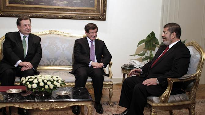 FILE - In this Monday, July 2, 2012 file photo, Turkish Ambassador to Egypt, Hussein Awny, left, and Turkish Foreign Minister Ahmet Davutoglu, center, meet with Egyptian President Mohammed Morsi, right, at the Presidential Palace in Cairo, Egypt. Egyptian President Mohammed Morsi will travel to Turkey on Sunday, Sept. 30, 2012 to try to strengthen an emerging alliance of two moderate Islamist governments in a region beset by conflict and instability.(AP Photo/Maya Alleruzzo, File)
