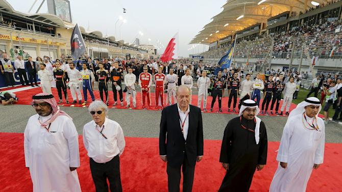 Officials pose for a group photo with Formula One Drivers behind them during Bahrain's F1 Grand Prix
