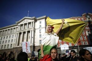 Protester wrapped in Bulgarian national flag shouts anti-government slogans in front of the government building in central Sofia