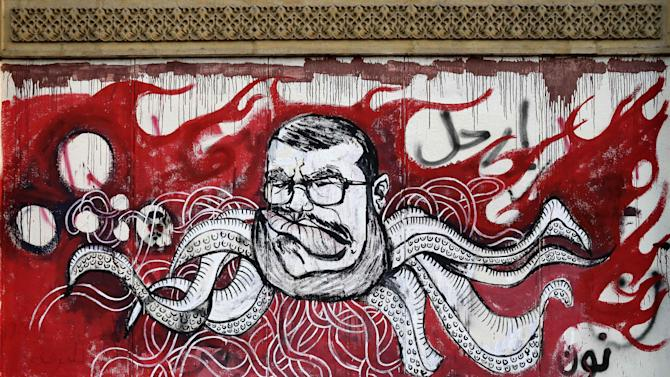 FILE - In this Saturday, Dec. 8, 2012 file photo, Graffiti depicting Egyptian President Mohamed Morsi covers an outer wall of the presidential palace in Cairo, Egypt. Some six months since becoming the first democratically elected president of Egypt, Morsi is widely accused of having abandoned pledges of inclusive government for doctrinaire and authoritarian ways. (AP Photo/Hassan Ammar, File)