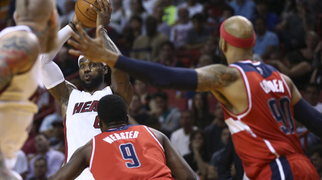 Miami Heat's LeBron James (6) looks to pass under the pressure of Washington Wizards defenders Martell Webster (9) and Drew Gooden (90) during the first half of an NBA basketball game in Miami, Mo