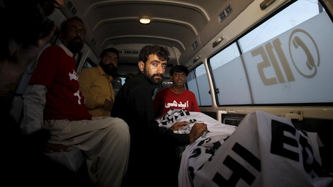 Abdul Majeed, brother of Shafqat Hussain who was convicted of killing a child in 2004, sits in an ambulance beside the body of Safqat after his execution in Karachi, Pakistan