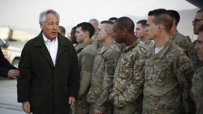 U.S. Secretary of Defense Chuck Hagel, left, greets U.S. Army troops on the tarmac of Kabul airport, March 11, 2013 before boarding a flight to Washington. Hagel encountered political tension with the Afghan president and a series of security problems during his first visit to Afghanistan as Pentagon chief, but he met privately with President Hamid Karzai and says they discussed the key issues. (AP Photo/Jason Reed, Pool)