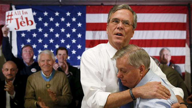 Republican U.S. presidential candidate Jeb Bush embraces Senator Lindsey Graham after Graham introduced him at a town hall in Salem, New Hampshire