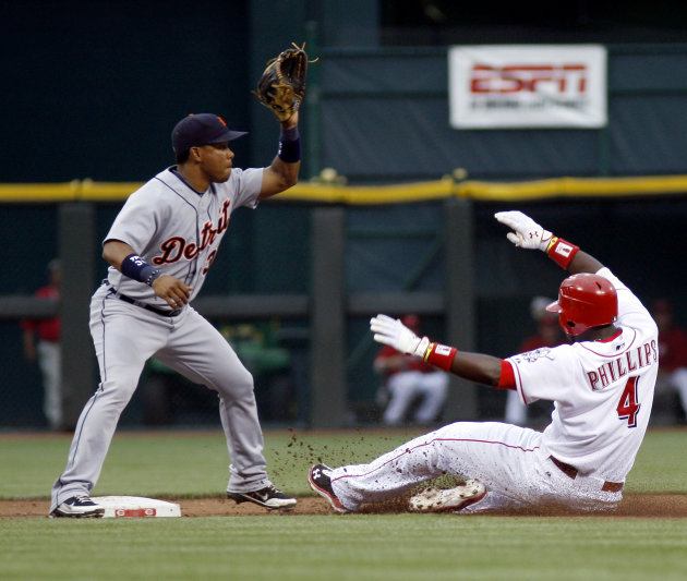 Cincinnati Reds' Brandon Phillips (4) slides safely into second base for a double beating the tag from Detroit Tigers shortstop Ramon Santiago in the second inning of a baseball game, Sunday, June 10,