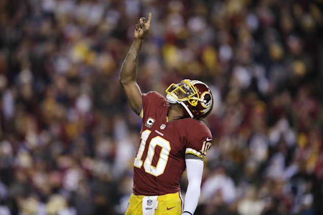 Washington Redskins quarterback Robert Griffin III celebrates a touchdown during the first half of an NFL football game against the Dallas Cowboys on Sunday, Dec. 30, 2012, in Landover, Md. (AP Photo/