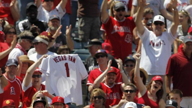 Los Angeles Angels' Albert Pujols (5) heads into the dugout after a two-run home run with Mike Trout against the Toronto Blue Jays during the fifth inning of a baseball game in Anaheim, Calif., Sunday, May 6, 2012. This was Pujols' first home run of the season. (AP Photo/Chris Carlson)