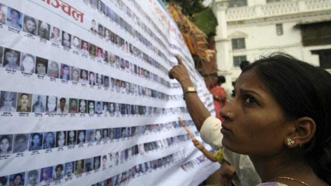 File photo taken on Agust 30, 2010 shows people looking at photographs of missing people who disappeared during Nepal's decade-long Maoist insurgency in Kathmandu