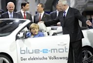 Chancellor Angela Merkel inspects an electric car during a visit to the Volkswagen plant in Wolfsburg, central Germany, in April. Europe&#39;s biggest car maker, said Thursday that bottom-line profits in the first half of the year soared by more than a third, leading it to confirm its upbeat forecast for 2012