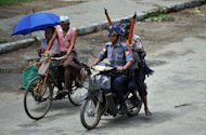 Myanmar police patrol the streets of Sittwe following religious unrest on June 11, 2012. In both Rakhine and Meiktila, the government later declared a state of emergency for the affected areas and sent in government troops after police and other local security forces failed to stem the bloodshed