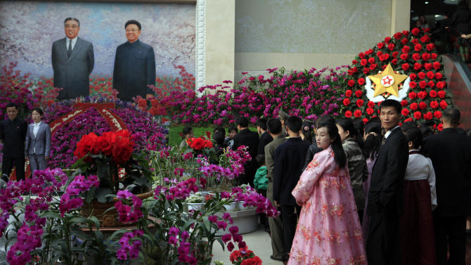 "A couple looks back as they stand in line to pose for a picture in front of portraits of the late leaders Kim Il Sung and Kim Jong Il at a festival for the ""Kimilsungia"" flower to mark 100 years since the birth of North Korea's late leader in Pyongyang, North Korea, Tuesday, April 17, 2012. (AP Photo/Ng Han Guan)"