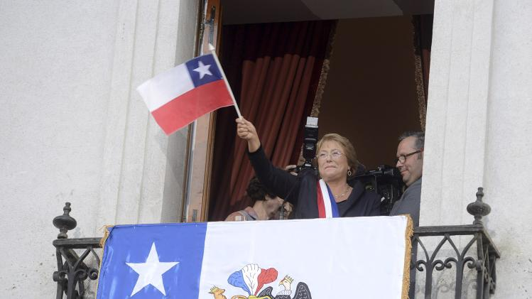 Chile's President Bachelet greets to supporters with a chilean flag after a speech from the balcony of the La Moneda Presidential Palace in Santiago
