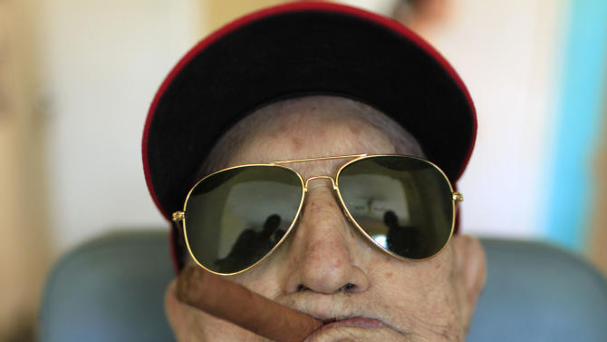 Conrado Marrero, the world's oldest living former major league baseball player, poses for a photo during his 102nd birthday bash at his home in Havana, Cuba, Thursday, April 25, 2013. In addition to his longevity, the former Washington Senator has much to celebrate this year. After a long wait, he finally received a $20,000 payout from Major League baseball granted to old-timers who played between 1947 and 1979. The money had been held up since 2011 due to issues surrounding the 51-year-old U.S. embargo on Cuba, which prohibits most bank transfers to the Communist-run island. But the payout finally arrived in two parts, one at the end of last year, and the second a few months ago, according to Marrero's family. (AP Photo/Franklin Reyes)