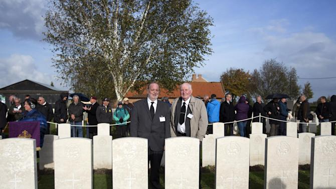 Peter Allcock, left, and Keith Allcock, relatives of World War I soldier Pvt. Herbert Ernest Allcock stand in back of his gravestone during a re-burial ceremony in Bois-Grenier, France, Wednesday, Oct. 22, 2014. Fifteen British WWI soldiers were re-buried at Y Farm Commonwealth cemetery on Wednesday, nearly a century after they died in battle. The soldiers, who served with the 2nd Battalion, York and Lancaster Regiment, were discovered in a field nearby in Beaucamps-Ligny in 2009 and identified through a variety of means, including DNA. Out of the 15 soldiers found, 11 were positively identified. Pvt. Herbert Ernest Allcock was one of the soldiers identified. (AP Photo/Virginia Mayo)
