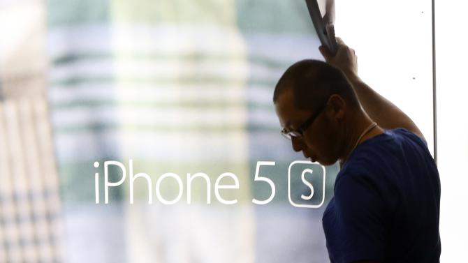 A staff of Apple store removes a display poster of iPhone 5S as they prepare for Apple's new iPhone 6 and 6 Plus sale at Tokyo's Omotesando shopping district