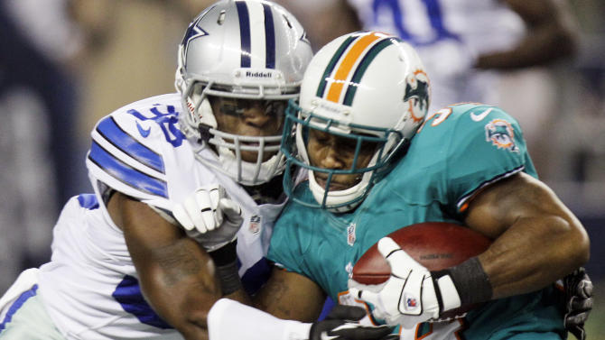 Dallas Cowboys' Eddie Whitley, left, tackles Miami Dolphins running back Marcus Thigpen during the first half of a preseason NFL football game, Wednesday, Aug. 29, 2012, in Arlington, Texas. (AP Photo/LM Otero)