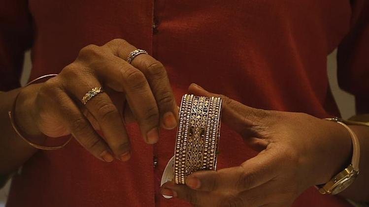 An employee shows a gold bangle to a customer inside a jewellery showroom in Mumbai