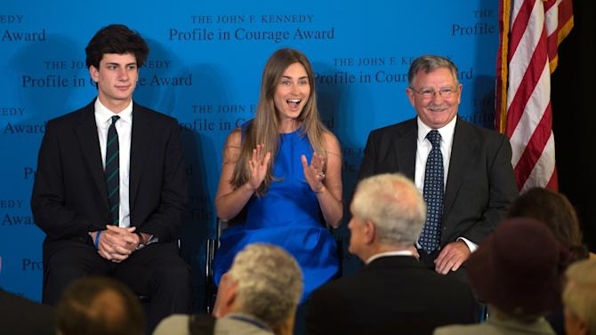 Lauren Bush Lauren, center, granddaughter of former President George H.W. Bush, center, reacts to seeing family members in the audience before she accepts the 2014 John F. Kennedy Profile in Courage Award on behalf of her grandfather from Jack Schlossberg, grandson of President John F. Kennedy, left, as fellow Profile in Courage Award recipient, Paul W. Bridges, looks on during a ceremony at the John F. Kennedy Library and Museum Sunday, May 4, 2014, in Boston. (AP Photo/Gretchen Ertl)