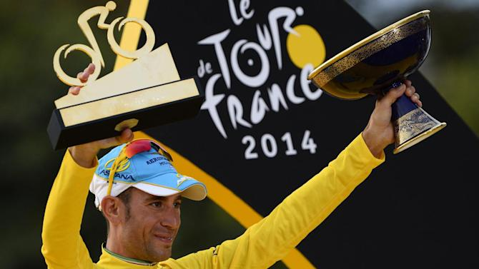 Vincenzo Nibali, winner of the 2014 Tour de France, celebrates with his trophies on the podium on the Champs-Elysees avenue in Paris on July 27, 2014